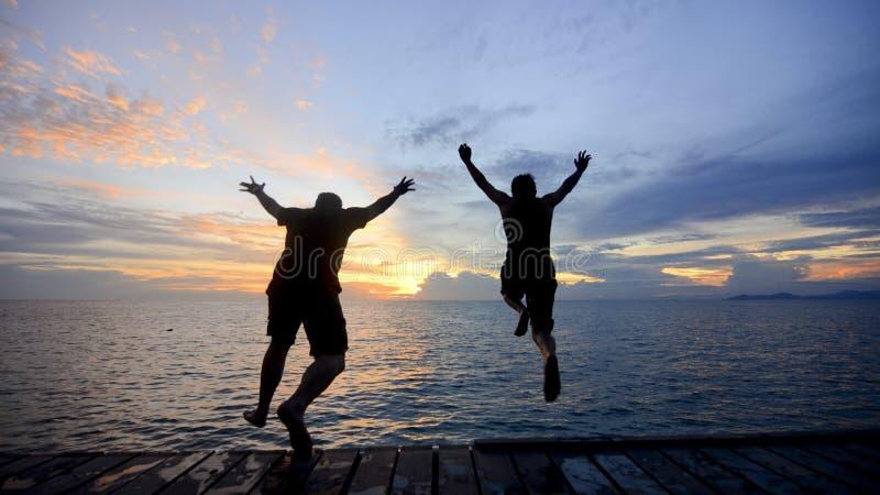 Silhueta de um amigo que salta no mar durante o por do sol dourado foto de stock royalty free