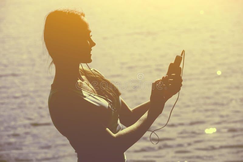A silhueta de um atleta fêmea novo no fato de esporte que escuta a música em um smartphone no verão, durante a manhã exercita imagem de stock royalty free