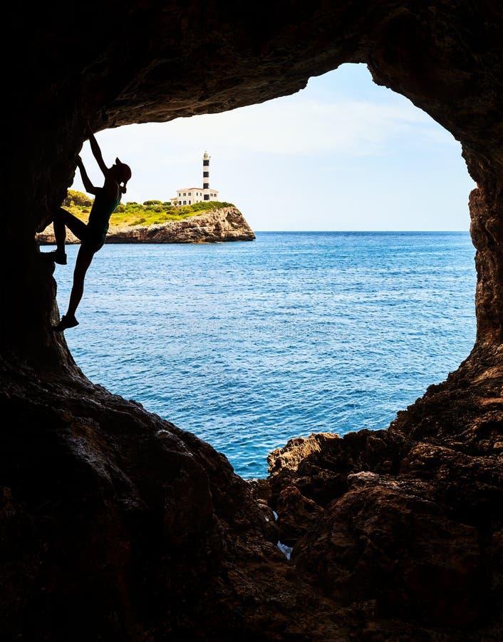Silhueta de um atleta fêmea que escala em uma caverna imagem de stock royalty free