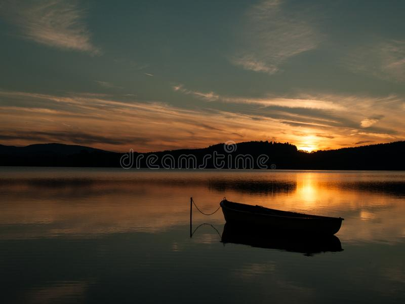 Silhueta de um barco em um lago com por do sol imagem de stock royalty free