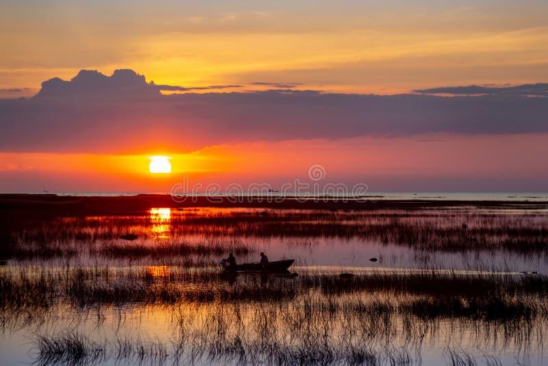 Silhueta de um barco de pesca no lago na perspectiva de um céu bonito do por do sol refletido na água fotografia de stock