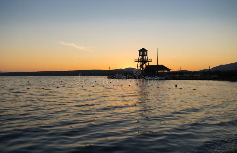 A silhueta de um cais e de uma linha costeira do lago no por do sol foto de stock