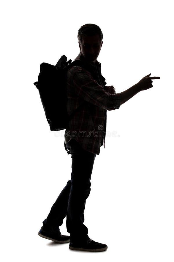 Silhueta de um caminhante ou de um guia tur?stica masculino que apontam em algo imagem de stock
