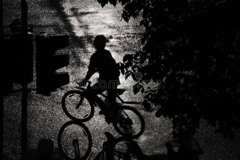 Silhueta de um ciclista na chuva fotografia de stock