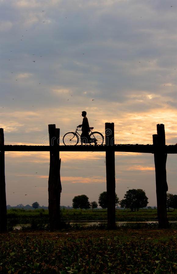 Silhueta de um ciclista na ponte de U Bein no por do sol imagens de stock royalty free