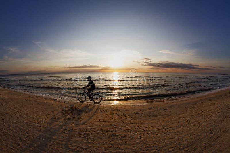 Silhueta de um ciclista no por do sol imagens de stock royalty free