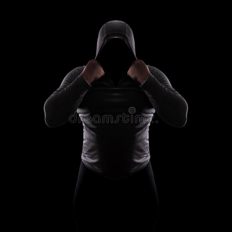 Silhueta de um clube masculino da luta em uma capa sem uma cara Silhueta do assediador no fundo preto, em incógnito, anônimo, per foto de stock