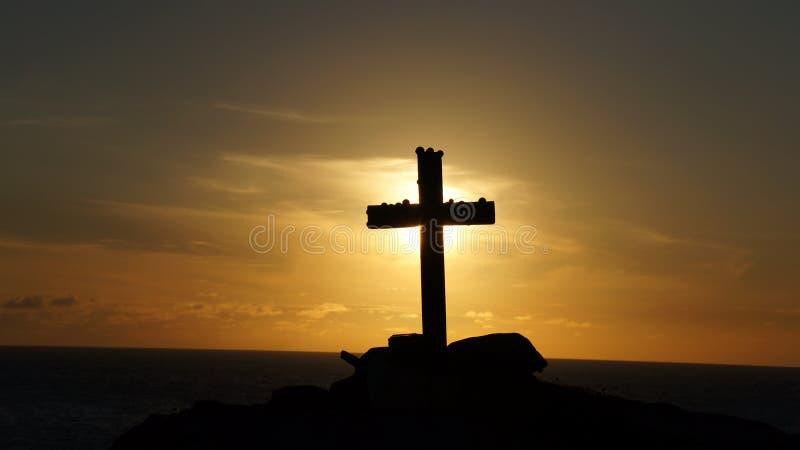 Silhueta de um crucifixo transversal religioso contra um por do sol foto de stock