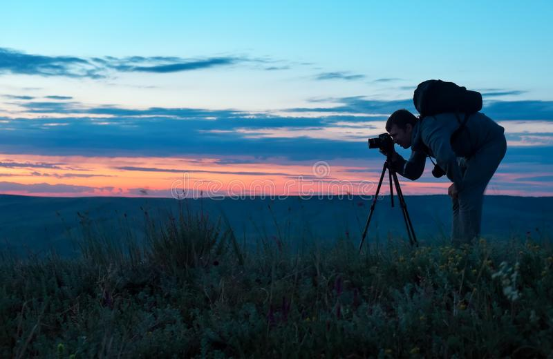 Silhueta de um fotógrafo profissional que usa um tripé, tomando uma foto imagens de stock royalty free