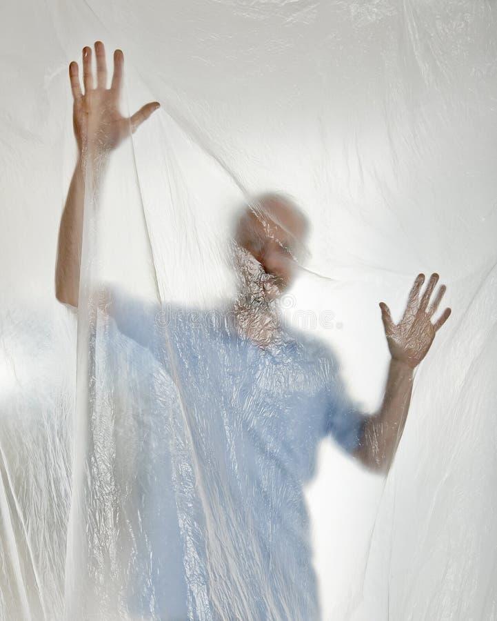 Silhueta de um homem atrás do plástico imagens de stock