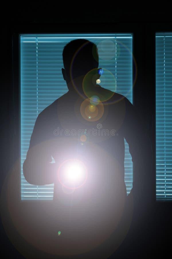 Silhueta de um homem com lanterna elétrica foto de stock royalty free