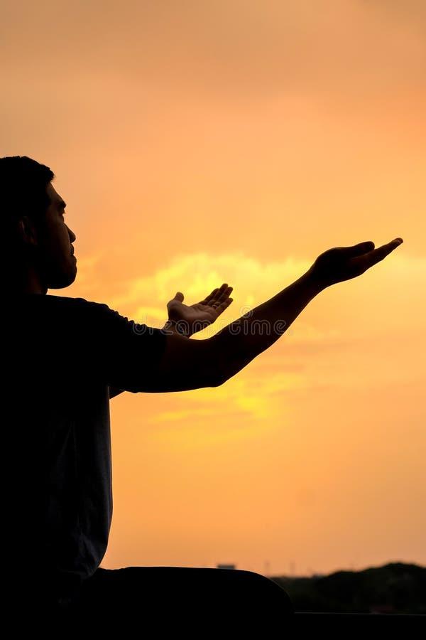 Silhueta de um homem com mão acima no por do sol imagens de stock