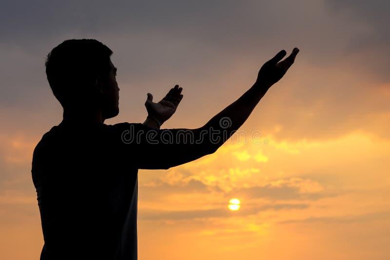 Silhueta de um homem com mão acima no por do sol imagens de stock royalty free