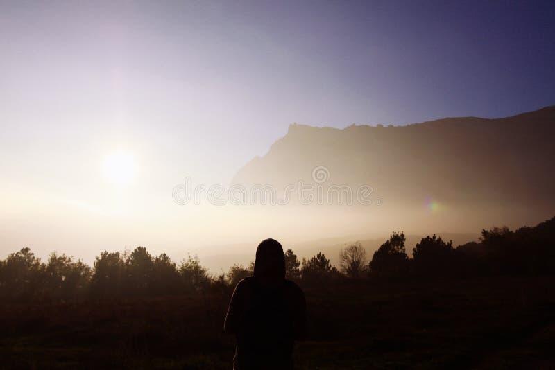 Silhueta de um homem contra o contexto de montanhas enevoadas Silhueta fêmea no fundo de montanhas enevoadas fotografia de stock