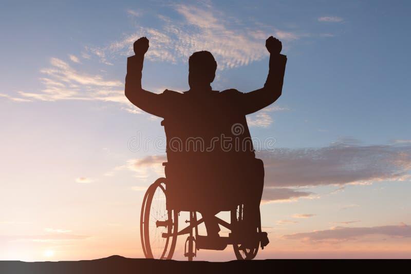Silhueta de um homem deficiente na cadeira de rodas fotografia de stock
