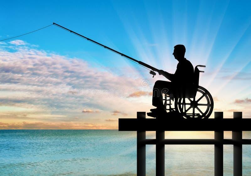 Silhueta de um homem dos enfermos em uma cadeira de rodas com uma vara de pesca em sua pesca da mão perto da água no cais imagens de stock