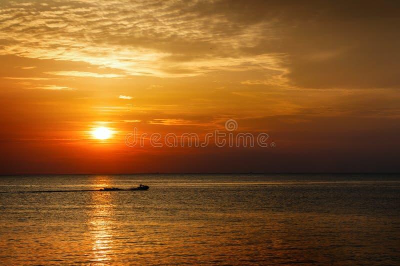 Silhueta de um homem em um esqui do jato no mar no por do sol imagem de stock