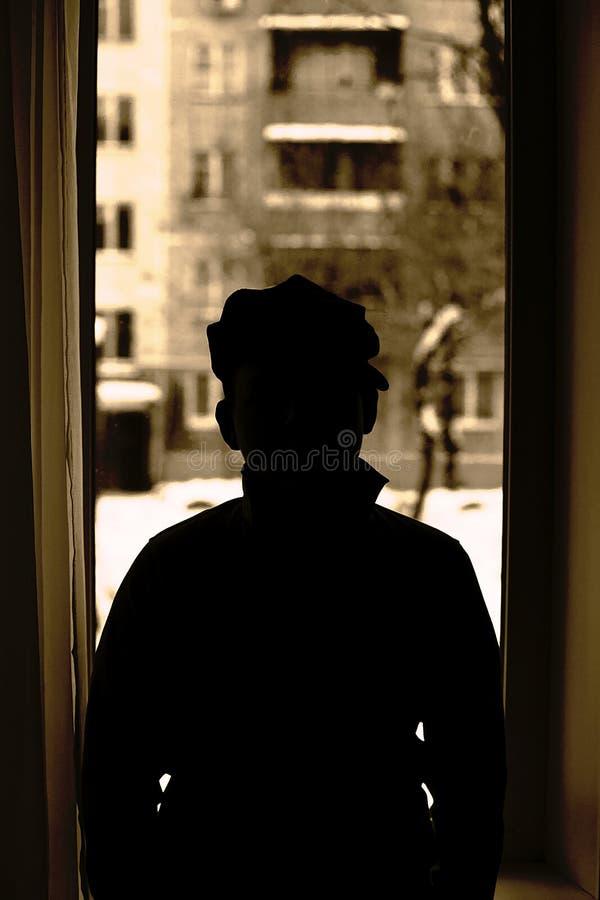 Silhueta de um homem em uma janela imagens de stock