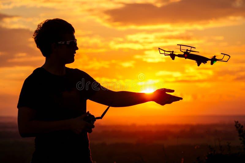 A silhueta de um homem lança um drone com um controle remoto à luz do sol fotos de stock