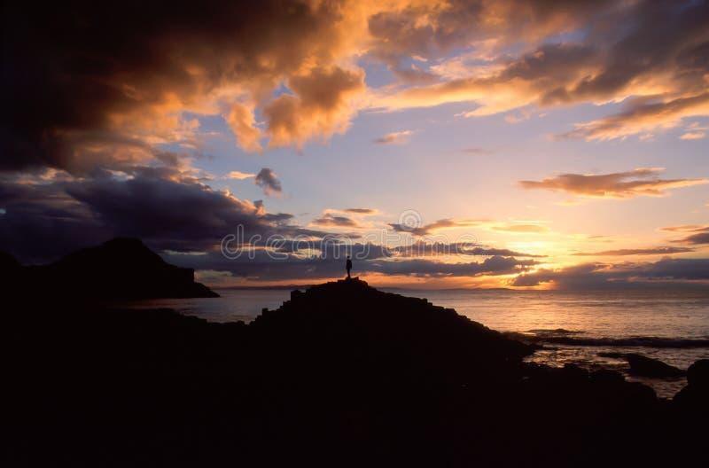 A silhueta de um homem no cenário natural de um por do sol sobre imagens de stock