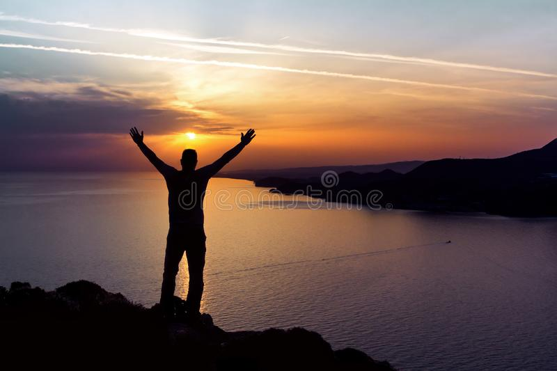 Silhueta de um homem no fundo do sol do por do sol no mar imagem de stock royalty free