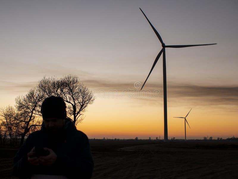 Silhueta de um homem no por do sol que faz uma foto das turbinas eólicas Plantas de energias eólicas no por do sol imagem de stock royalty free