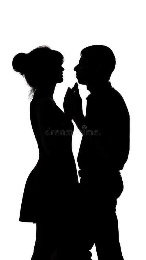 Silhueta de um homem novo e fêmea no amor no fundo isolado branco, nas mãos do toque do homem da mulher e na dança lentamente, co imagem de stock royalty free