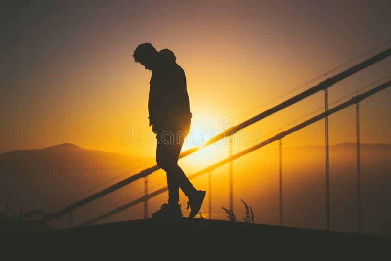 Silhueta de um homem novo que anda na escadaria atrás dos trilhos da escada com opinião bonita do por do sol fotos de stock