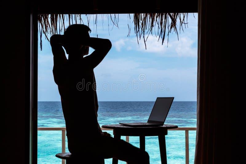 Silhueta de um homem novo que relaxa ao trabalhar com um computador em uma tabela ?gua tropical azul clara como o fundo imagens de stock royalty free