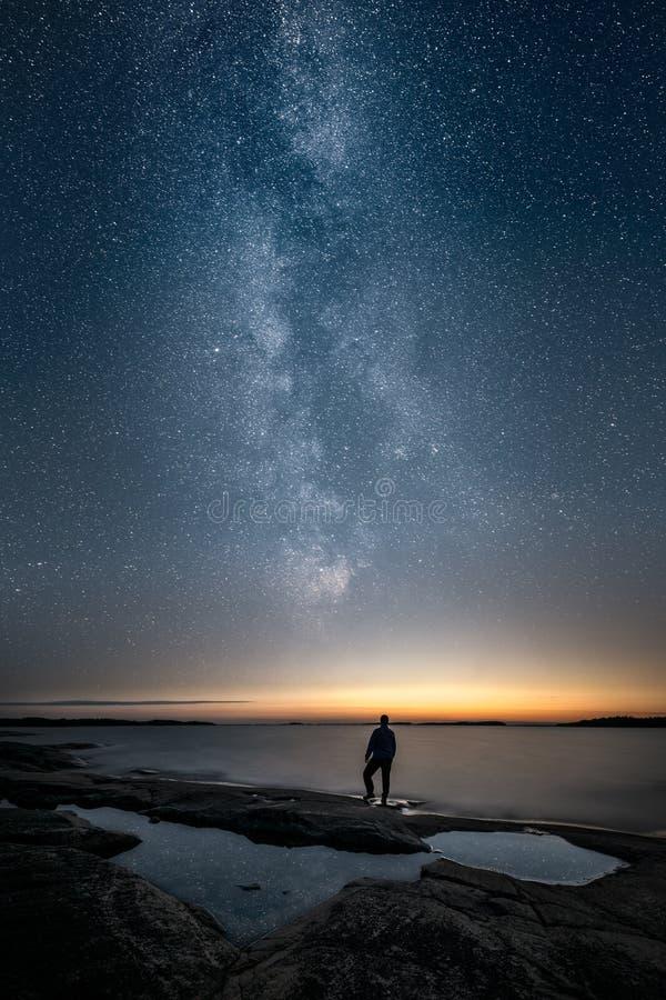 Silhueta de um homem que está apenas por um mar e que olha acima a Via Látea fotografia de stock