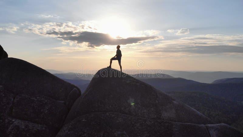 A silhueta de um homem que está triunfantemente em uma parte superior da montanha no por do sol fotografia de stock