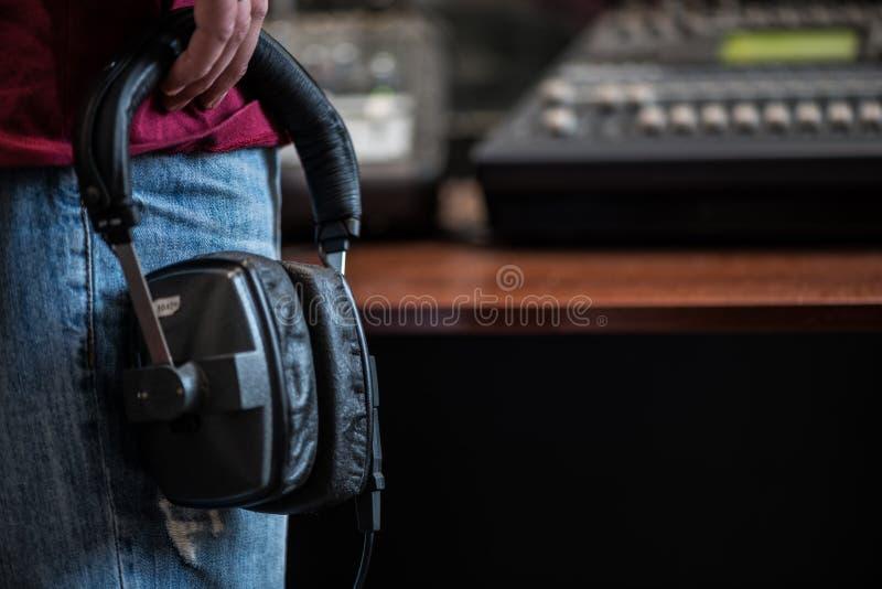 Silhueta de um homem que guarda fones de ouvido nos estúdios de rádio fotografia de stock royalty free