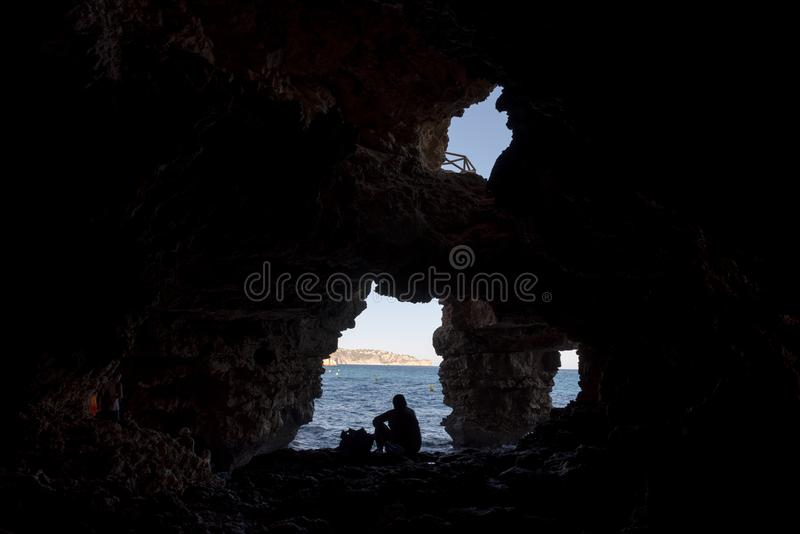 Silhueta de um mergulho na água, vista do homem de uma caverna foto de stock royalty free