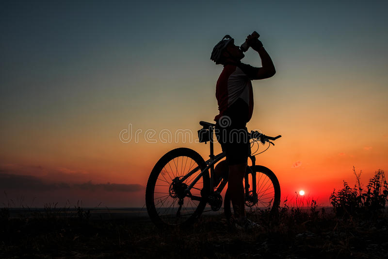 Silhueta de um motociclista e de uma bicicleta no fundo do céu imagens de stock