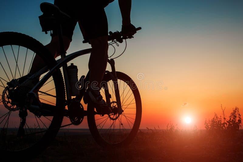 Silhueta de um motociclista e de uma bicicleta no fundo do céu fotos de stock royalty free