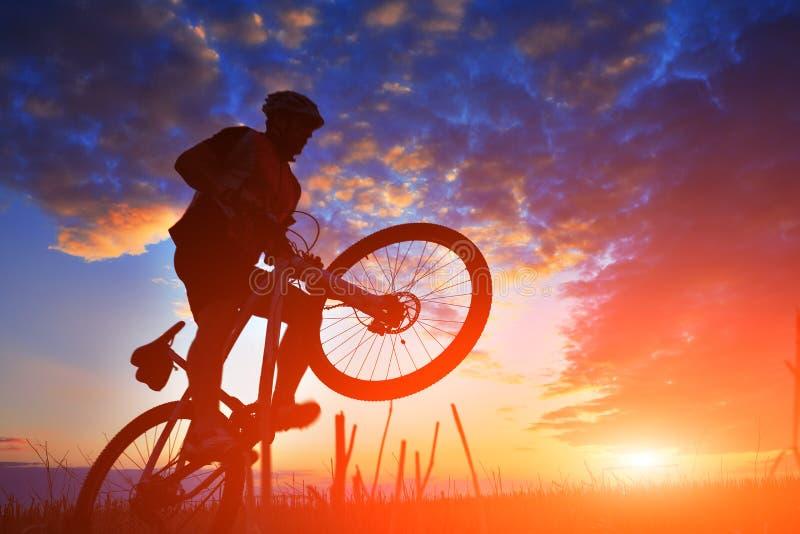 Silhueta de um motociclista e de uma bicicleta no fundo do por do sol fotografia de stock royalty free