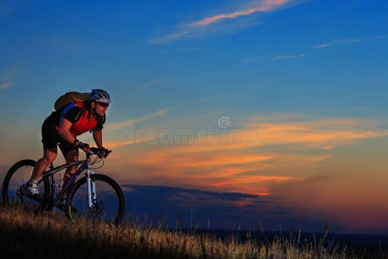 Silhueta de um motociclista e de uma bicicleta no fundo do por do sol fotos de stock