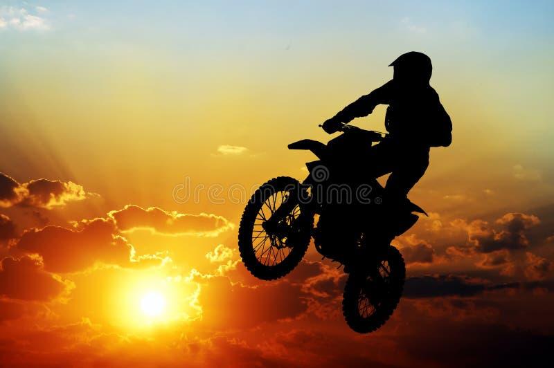 Silhueta de um motociclista em um fundo do céu escuro imagens de stock royalty free