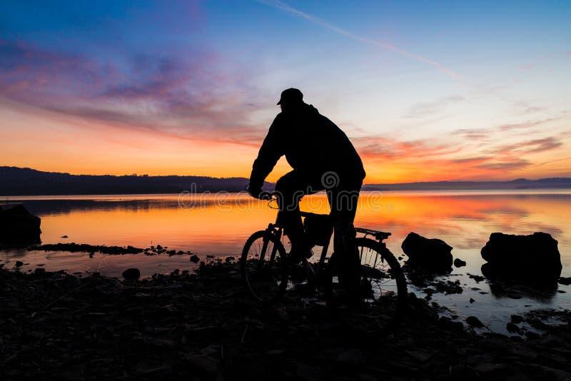 Silhueta de um Mountain bike e de um ciclista no nascer do sol fotos de stock