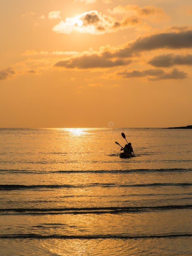 Silhueta de um par bonito em um barco da canoa durante o por do sol foto de stock