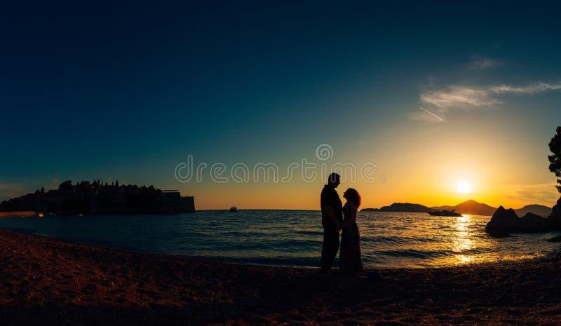 Silhueta de um par do recém-casado no mar no por do sol Casamento dentro fotografia de stock royalty free