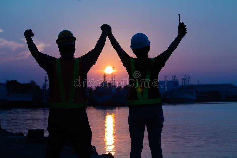 Silhueta de um par esposos dos coordenadores que guardam as mãos junto com alegre no cais Trabalhador foto de stock royalty free