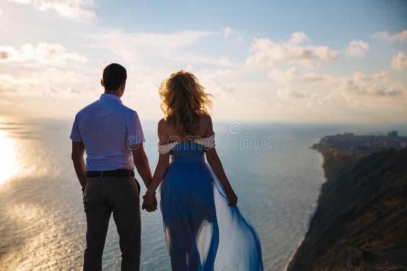 Silhueta de um par loving no por do sol Homem que abraça com uma mulher em uma montanha alta que negligencia o mar Conceito imagem de stock royalty free