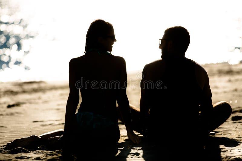 Silhueta de um par no amor na praia no por do sol História de amor Homem e uma mulher na praia imagens de stock royalty free