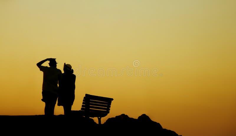 Silhueta de um par no amor na praia no por do sol História de amor Homem e uma mulher na praia Pares bonitos na luz solar imagens de stock