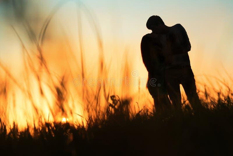 Silhueta de um par novo que beija no por do sol imagens de stock royalty free