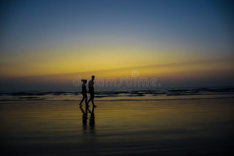 Silhueta de um par que anda em uma praia na Índia no crepúsculo imagens de stock royalty free