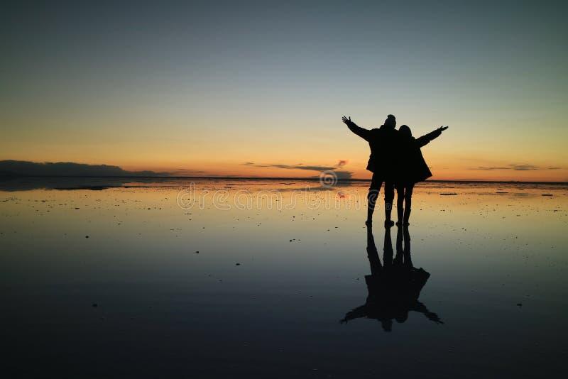 Silhueta de um par que aumenta seus braços para o momento feliz no efeito incrível de planos de sal de Uyuni, Bolívia do espelho fotografia de stock