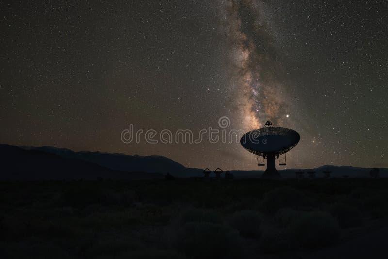 Silhueta de um prato de rádio alinhado com a galáxia da Via Látea foto de stock