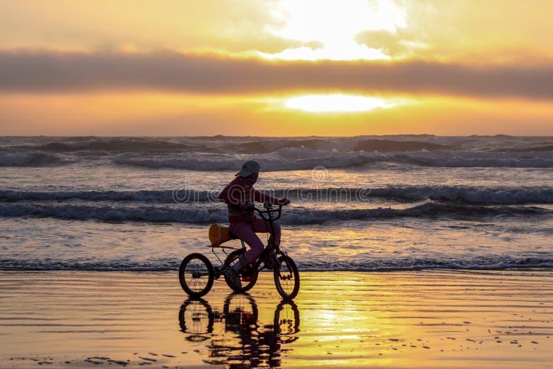 Silhueta de um triciclo da equitação da menina em uma praia em uma maré começando imagens de stock